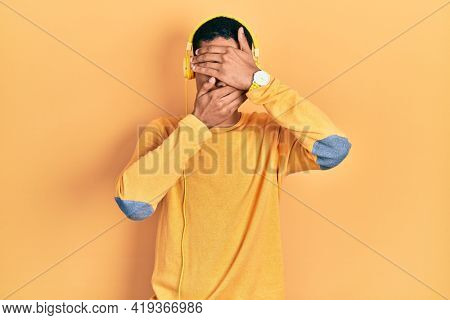Young african american guy listening to music using headphones covering eyes and mouth with hands, surprised and shocked. hiding emotion