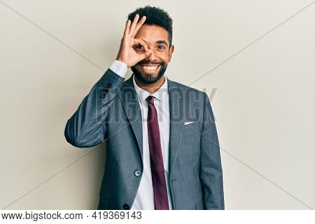 Handsome hispanic man with beard wearing business suit and tie doing ok gesture with hand smiling, eye looking through fingers with happy face.