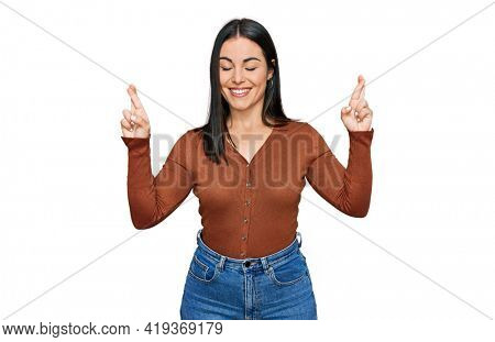 Young hispanic woman wearing casual clothes gesturing finger crossed smiling with hope and eyes closed. luck and superstitious concept.