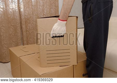 Moving. The Man Takes The Box From The Apartment To Move It. Stack Of Cardboard Boxes. Loader. Mover
