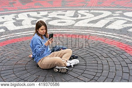 Young Woman In Blue Sweatshirt Uses Smartphone While Sitting On Street Cobbled Square, Modern Techno