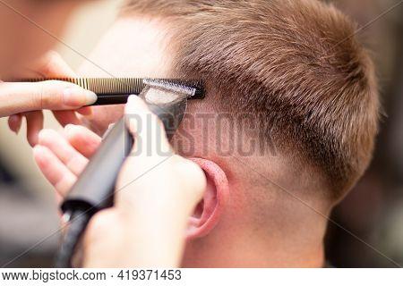 Men's Haircut. Hair Cutting Close-up. Haircut Of The Head. Trimmer Work.