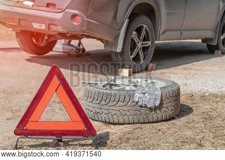 Stop Sign In Front Of The Car. Replacing The Wheel On The Road By The Driver. Replacement Of Tires O