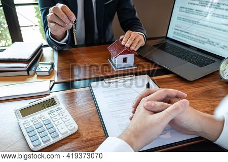 Real Estate Agent Are Presenting Home Loan And Sending Keys To Customer After Signing Contract To Bu