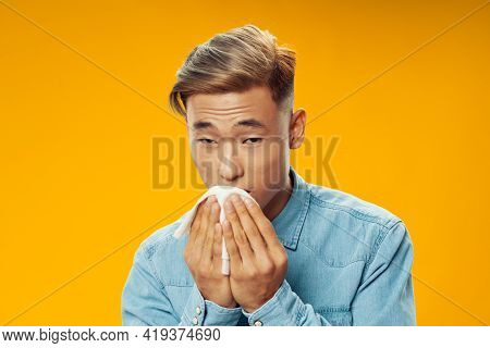 Man And Asian Appearance With A Handkerchief In His Hands A Cold Yellow Background