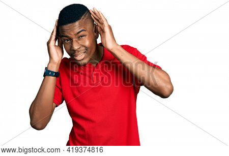 Young african american man wearing casual red t shirt trying to hear both hands on ear gesture, curious for gossip. hearing problem, deaf