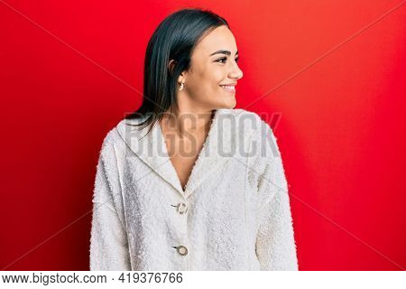 Young brunette woman wearing casual clothes looking to side, relax profile pose with natural face and confident smile.