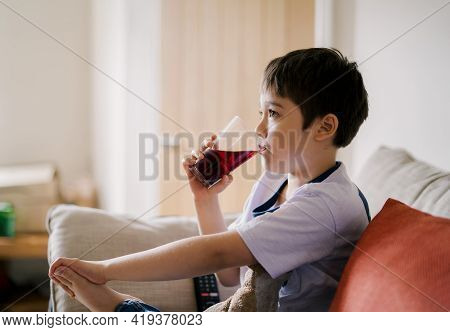 Kid Drinking Cranberry Juice From  Glass While Watching Tv, Healthy 7 Year Old Boy Sitting On Sofa D