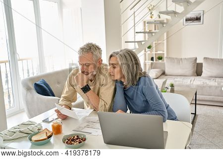 Worried Old Senior Couple Checking Bank Documents At Home. Serious Mature Retired Family Reading Pap