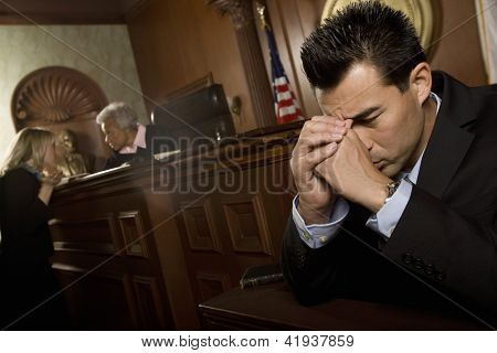 Unhappy lawyer sitting in courtroom