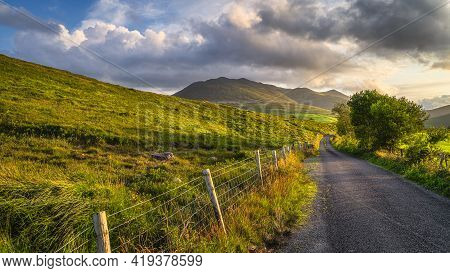Winding Country Road Leading Toward Highest Mountain In Ireland, Carrauntoohil In Macgillycuddys Ree