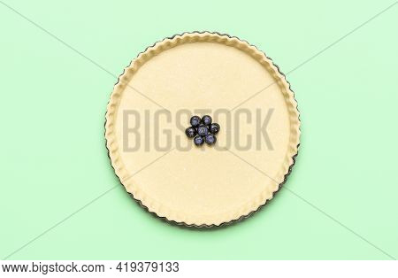Baking Blueberry Pie, Flat Lay. Uncooked Pie Crust And Blueberries Filling, On A Green Background.