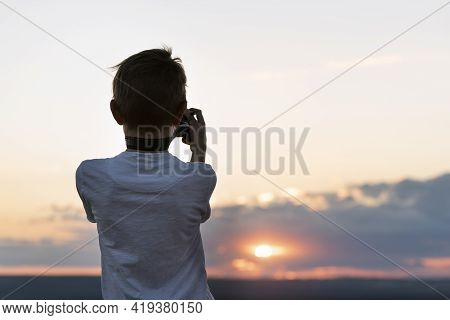 Boy Photographs The Sunset. Child With Camera On Setting Sun Background. Rear View.