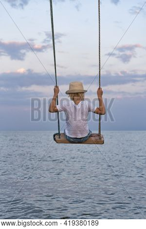 Boy In Straw Hat Riding On Swing Over The Water. Swing Against The Sky And The Sea.
