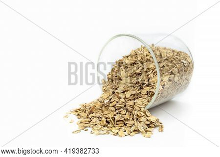 Oat Grains Falling From A Glass Recipient With White Background