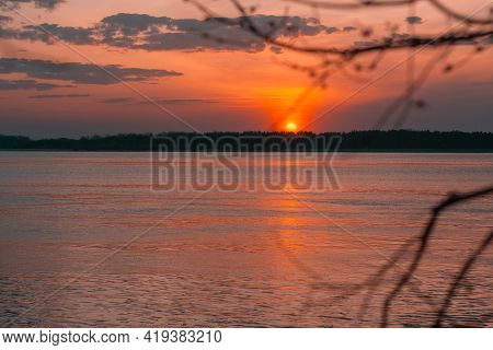 Sunset On The River On A Summer Evening. Calm Water In The Orange Rays Of The Sun. Local Tourism