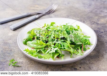 A Mixture Of Fresh Arugula, Chard And Mizun Leaves On A Plate And Forks On The Table. Vegetarianism,