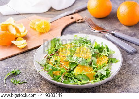 Diet Vegetarian Vitamin Salad Of Orange Slices And A Mix Of Arugula, Chard And Mizun Leaves On A Pla