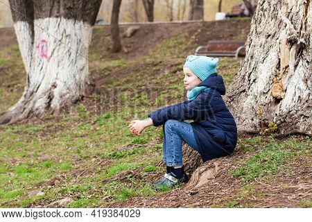 A Lonely Girl Sits In Solitude At The Root Of A Tree In The Park And Looks Into The Distance. Mental