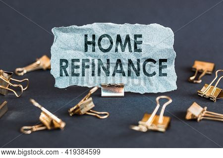 A Scrap Of Blue Paper With Clips On A Gray Background With The Text - Home Refinance.