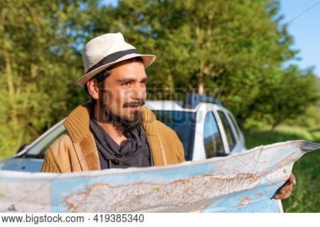 Latino Man With Hat Consulting A Map Leaning On His Off-road Suv Car. Person Doing Off-piste Route B