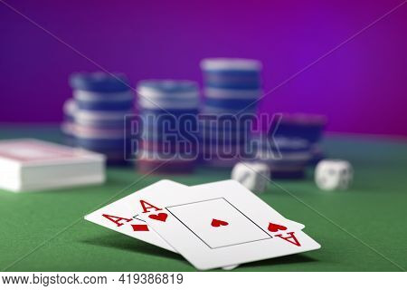 Two Aces And Stack Of Casino Chips In Background.
