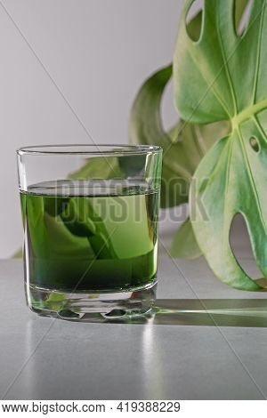 Chlorophyll Extract Is Poured In Pure Water In Glass Against A White Grey Background With Green Leaf