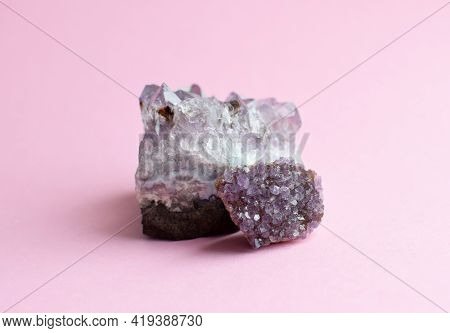 Beautiful Druses Of Natural Purple Mineral Amethyst  On A Pink Background. Large Crystals Of Preciou