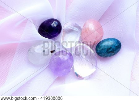 Gemstone Minerals On A Pink Background. Round Tumbling Minerals Of Amethyst, Rose Quartz, Rock Cryst
