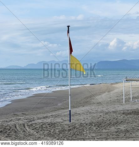 Red And Yellow Warning Flag On The Beach Of Forte Dei Marmi, Italy.