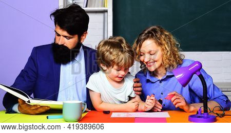 Parenting. Parents Helping Son To Make Homework. Family School. First Time To School.