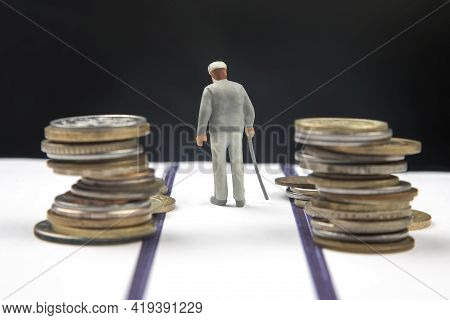 Miniature People. An Elderly Pensioner With A Stick Against The Background Of Money Walks The Road U