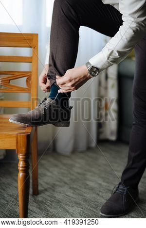 Groom Laces Up The Laces On The Shoes With His Foot On The Chair