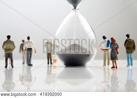 Miniature People. Different People Are Walking Next To The Hourglass On A White Background. Lifespan