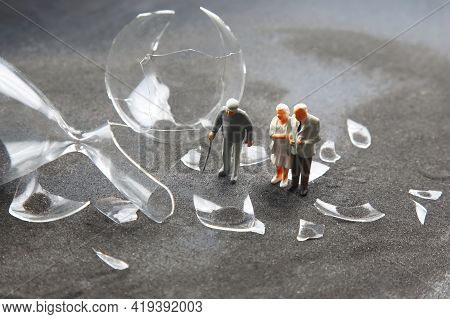Miniature People. Elderly People Walk Near The Broken Hourglass. Loss Of Life Time. Crisis Of Hope A