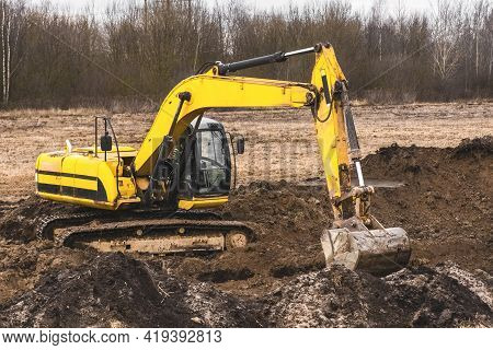 Construction Worker On An Crawler Excavator Equipment Digs A Trench In An Industrial Area. Excavatio