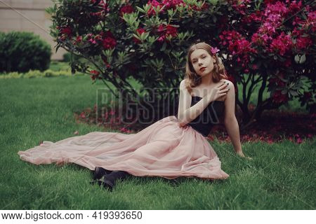 A Girl In A Long Pink Dress Sits In The Garden On The Grass Against A Background Of Pink Flowers. Sh