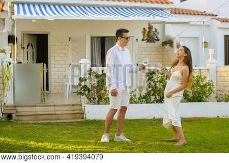 Beautiful Girl In A White Dress On A Date With A Man In White. Couple Celebrating Buying A House By