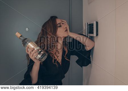 The Drunk Girl Came Home After The Party. Beautiful Woman On The Doorstep Tired With A Bottle Of Alc