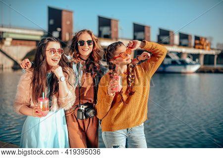 Three Girls Near The River Against The Sky Having Fun. Fashion Girls In Sunglasses. Jump, Rejoice, D