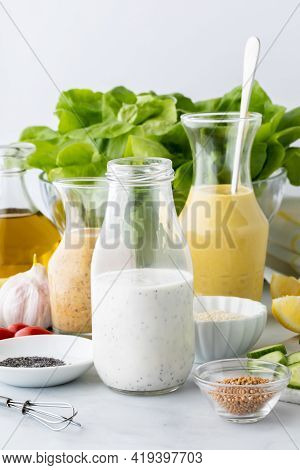 Close Up View Of Three Homemade Salad Dressings Surrounded By Various Ingredients In Making The Dres