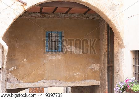 Barred Window Under The Arch. An Arch Under One Of The Houses In Barga. Details Of The Medieval City