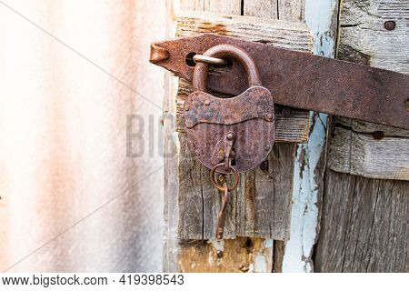 Iron Rusty Lock With A Key. Closed Door. Locked Gates To The Barn Lock. Old Locked Shutters.