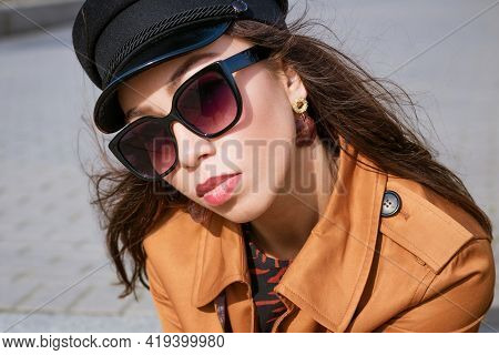 A Close-up Of A Female Portre Of Caucasian Appearance In Sunglasses And A Black Cap Looks Into The F