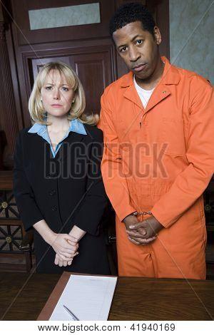 Portrait of dejected advocate standing with fettered prisoner