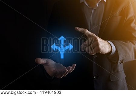 Businessman In A Suit Holds A Sign Showing Three Directions. In Doubt, Having To Choose Between Thre