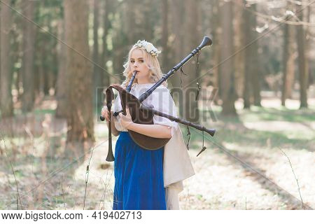 Beautiful Blonde Female In Slavic Clothes Playing The Flute And Pipe In The Summer Forest