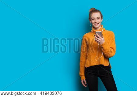 Young Ginger Woman With Freckles Is Listening To Music On A Blue Studio Wall With Free Space Using H