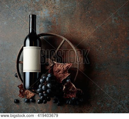 Bottle Of Red Wine With Grapes And Dried Vine Leaves On An Old Rusty Background. Top View With Copy