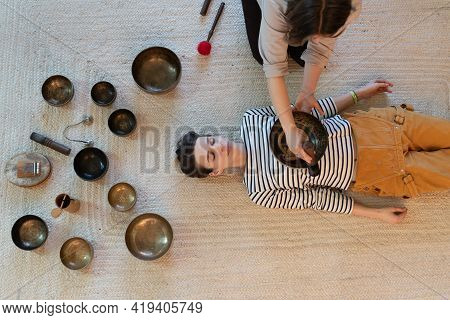 Tibetan Bowl Massage: Female Healer Masseuse Perform Traditional Tibetan Sound Singing Bowls Therapy